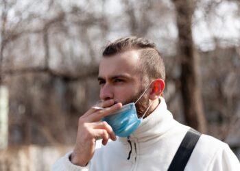 Junger Mann mit Maske raucht.