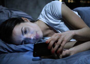 Eine Frau liegt im Bett und schaut auf ihr Smartphone.