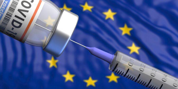Eine Spritze und eine Dosis COVID-19-Impfstoff vor der europäischen Flagge.