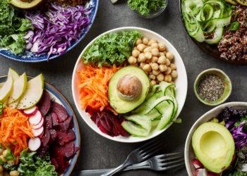 Mehrere Schüsseln mit verschiedenen pflanzlichen Speisen auf einem Tisch