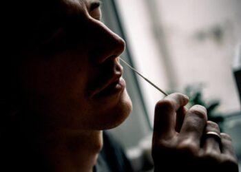 Ein Mann macht einen Nasen-Abstrich mit einem Wattestäbchen.