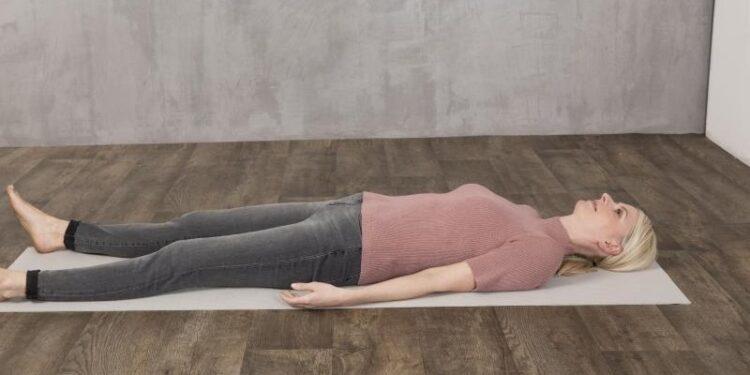 Eine Frau liegt auf einer Matte auf dem Boden.