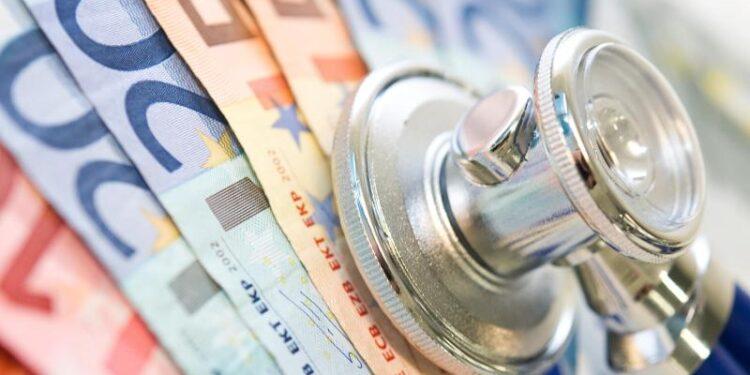 Ein Stethoskop liegt auf einigen Geldscheinen.