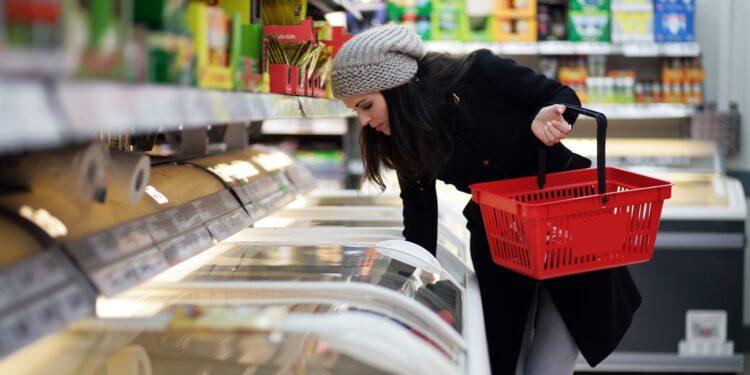 Eine Frau greift in die Tiefkühltruhe in einem Supermarkt.