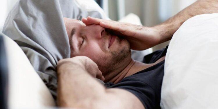 Ein Mann wacht gerade aus dem Schlaf auf.