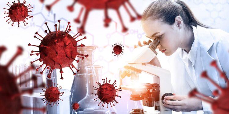 Eine Frau mit weißem Kittel sieht in ein Mikroskop.