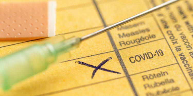 Spritze auf einem Impfausweis mit einem Kreuz bei COVID-19