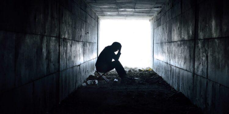 Eine Person sitzt am Ende eines dunklen Tunnels vor einem hellen Licht.