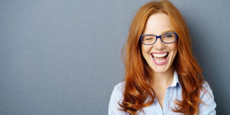 Rothaarige Frau mit Brille zwinkert mit einem Auge