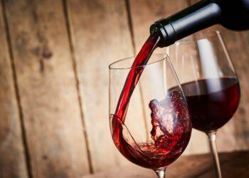 Aus einer Flasche wird Rotwein in ein Weinglas gegossen