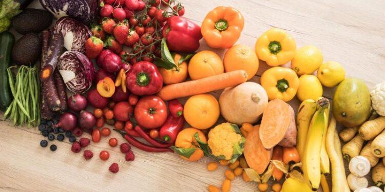 Eine Auswahl an Obst und Gemüse auf einer hölzernen Oberfläche.