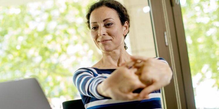 Eine Frau sitzt am Computer und streckt die Finger.