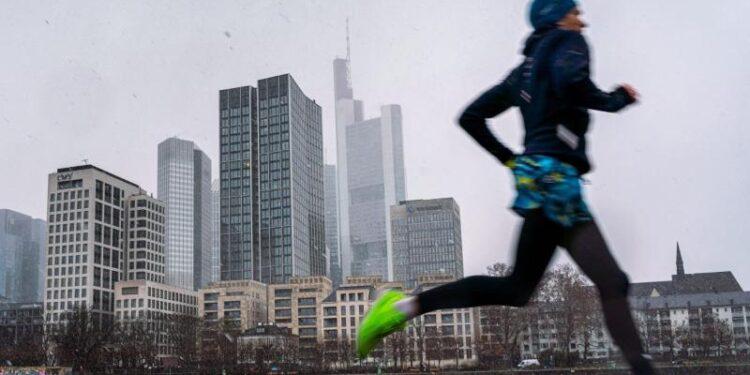 Ein Jogger läuft vor der Skyline von Frankfurt.