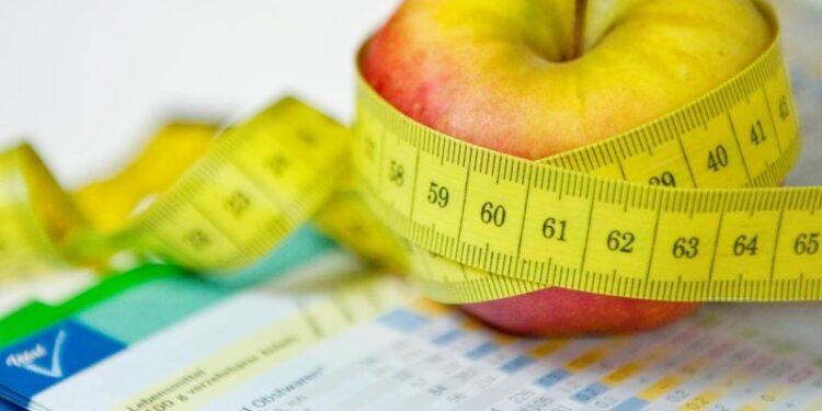 Ein Apfel und ein Maßband liegen neben einem Ernährungsplan.