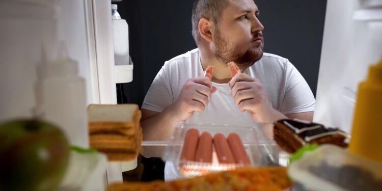 Ein Mann steht vor einem Kühlschrank und isst ein Würstchen.