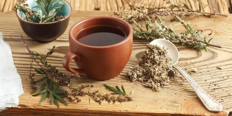Ein Beifuß-Tee steht auf einem Holzbrett umringt von getrockneten Beifuss-Kräutern.