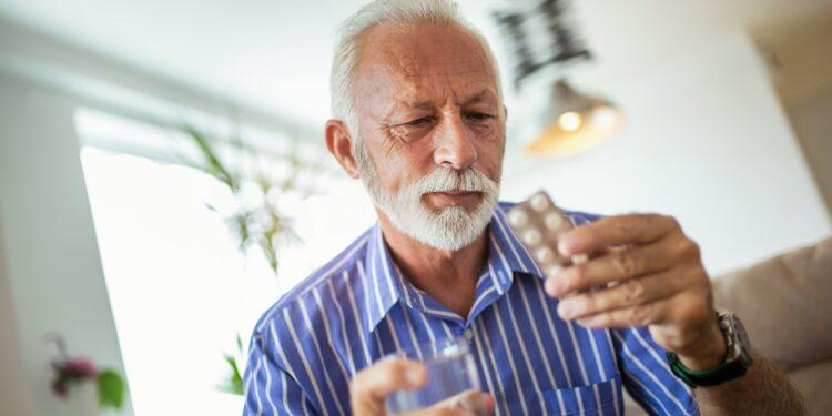 Mann hält seine blutdrucksenkenden Medikamente in der Hand und betrachtet sie.