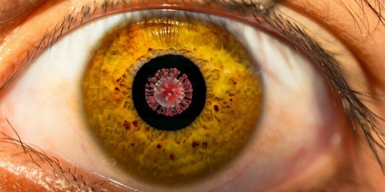 Großaufnahme vom Auge mit Coronaviurs in der Pupille.