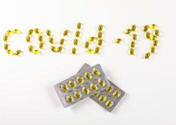 """Vitamin D-Pillen wurden so angeordnet, dass sie das Wort """"COVID-19"""" bilden."""