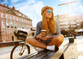 Junge Frau sitzt mit einem Einwegbecher vor ihrem Fahrrad