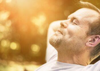 Mann entspannt mit geschlossen Augen in der Sonne.