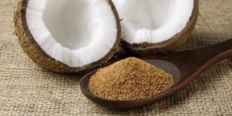 Kokosblütenzucker in einem Holzlöffel vor einer halbierten frischen Kokosnuss