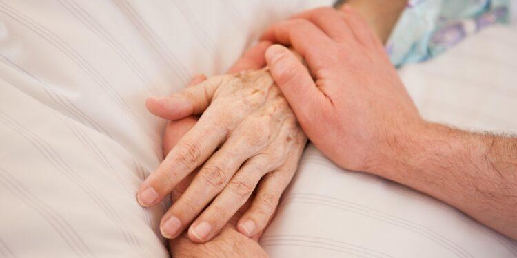 Die Hände einer Person halten die Hand einer im Bett liegenden Person.