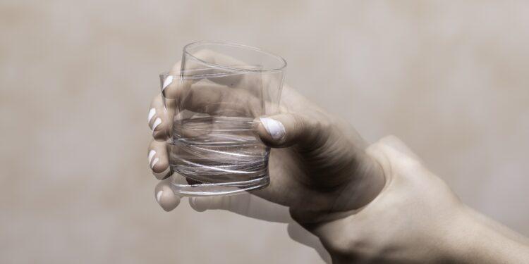 Eine zitternde Hand hält ein Glas mit Wasser fest.