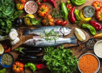 Verschiedene mediterrane Lebensmittel auf einer hölzernen Oberfläche.