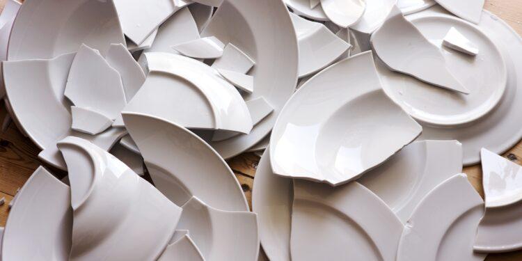 Zerbrochene Teller liegen auf einem Holzfußboden.