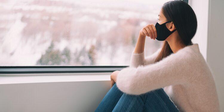 Eine Frau mit Mundschutz sitz vor einem Fenster und schaut nach draußen.