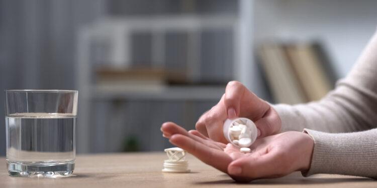 Ältere Frau schüttet Tabletten in ihre Hand