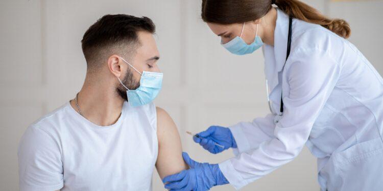 Mann wird von Ärztin geimpft