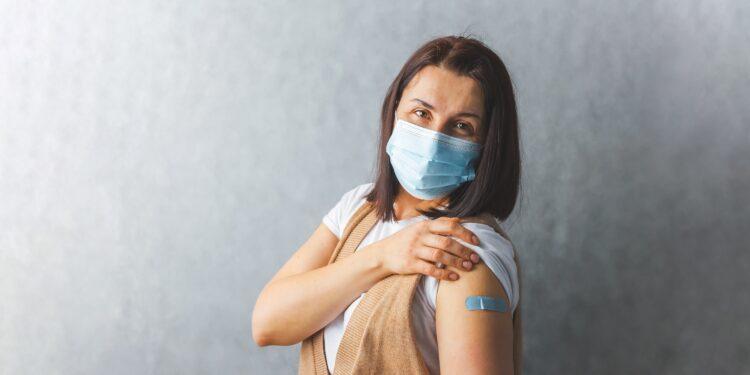 Frau mit medizinischer Maske zeigt ihr Pflaster auf dem Oberarm