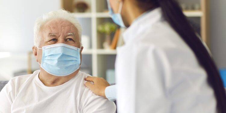 Ärztin und älterer Patient mit Mund-Nasen-Schutz