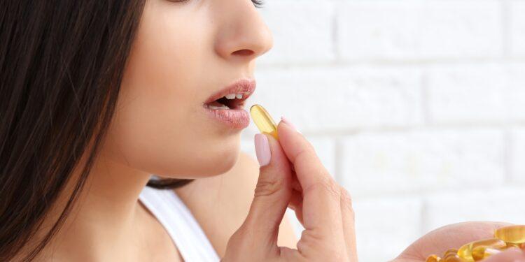 Młoda kobieta przyjmująca suplement diety