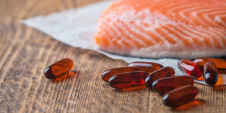 Omega-3-Pillen und ein Stück Lachs liegen auf einer hölzernen Oberfläche.