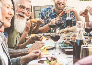Fröhliche Runde von Menschen beim Essen an einem Tisch im Freien.
