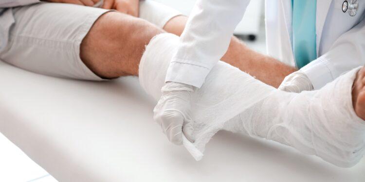 Arzt legt einen Gips um das Bein eines Patienten.