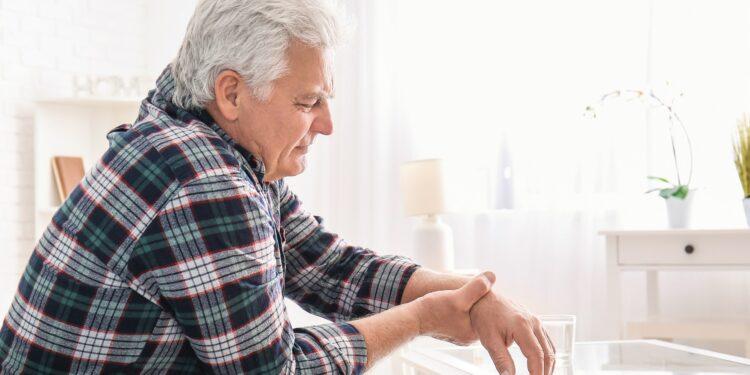Ein älterer Mann hält sein Handgelenk.
