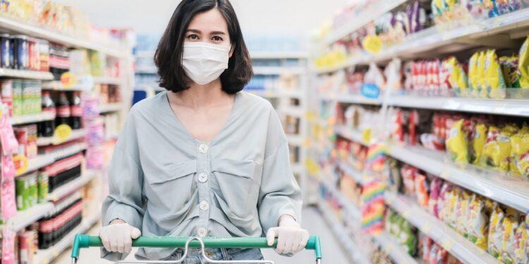 Frau mit Mund-Nasen-Schutz mit Einkaufswagen im Supermarkt