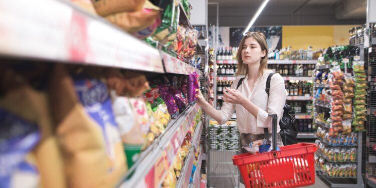 Eine Frau steht vor einem Regal mit Chips im Supermarkt.