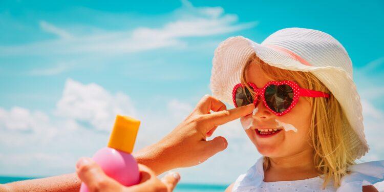 Frau cremt Mädchen mit Sonnenhut und Sonnenbrille das Gesicht mit Sonnenschutzcreme ein.