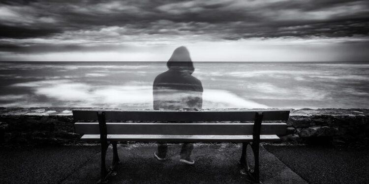 Eine halbdurchsichtige Person sitzt auf einer Parkbank und schaut aufs Meer.