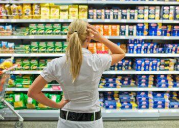 Eine Frau steht mit nachdenklicher Körperhaltung vor einem Regal im Supermarkt.