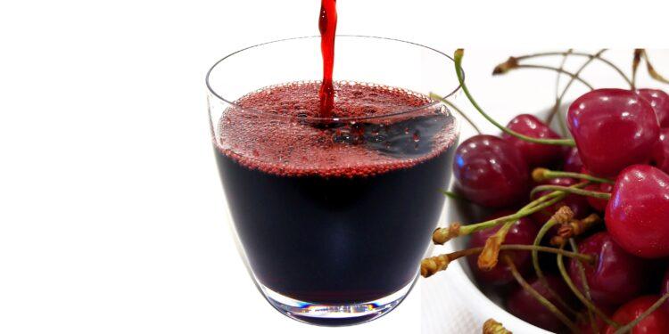 Kirschsaft wird in ein Glas gegossen, daneben steht eine Schale mit Kirschen