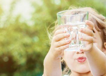 Mädchen hält mit beiden Händen ein Wasserglas nach oben