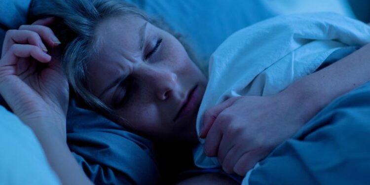 Eine Frau schläft mit gestresstem Gesichtsausdruck.
