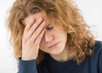 Eine gestresst aussehende Frau hält sich eine Hand an die Stirn.