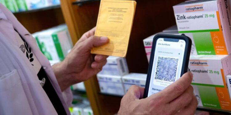 Ein Mann hält einen Impfpass in der einen und ein Smartphone in der anderen Hand.